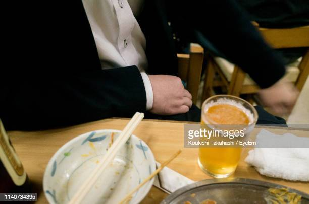 Midsection Of Man Having Beer At Restaurant