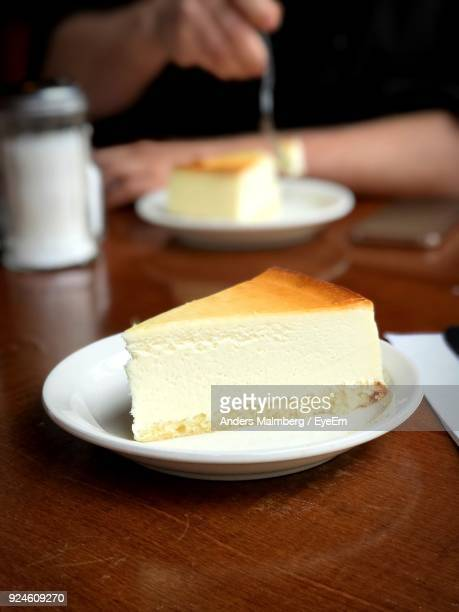 midsection of man having cake at table - cheesecake stock pictures, royalty-free photos & images