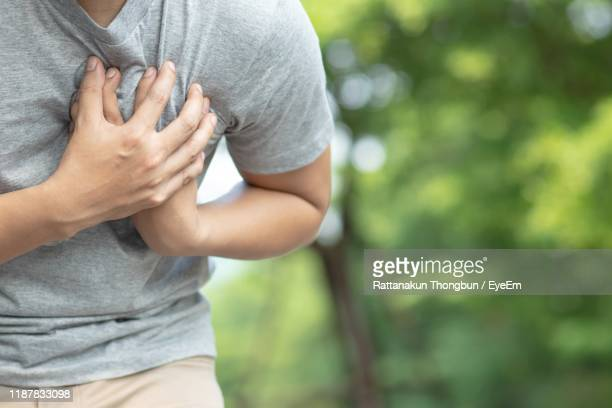 midsection of man having chest pain against trees - heart attack stock pictures, royalty-free photos & images