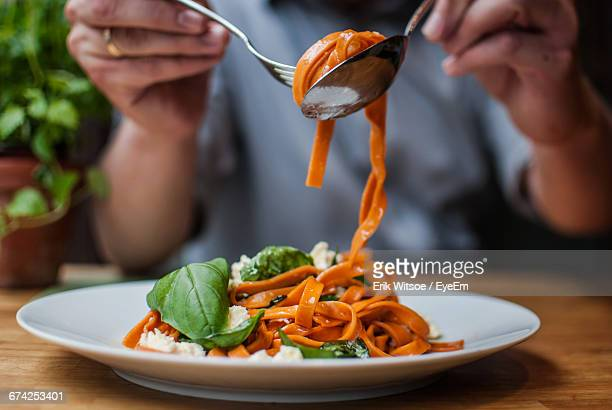 Midsection Of Man Having Pasta In Restaurant