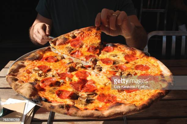 midsection of man having pizza at table in restaurant - pepperoni pizza stock photos and pictures