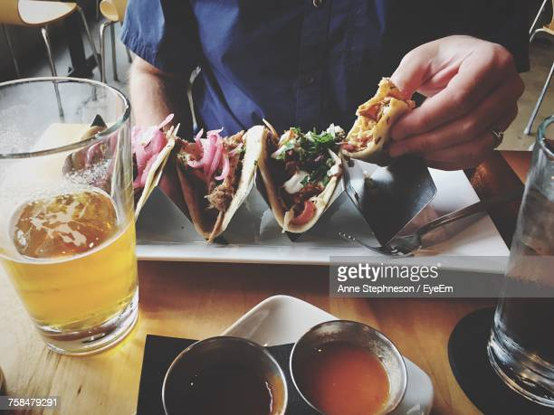 midsection of man having tacos and beer at table in restaurant - mexican beer stock pictures, royalty-free photos & images