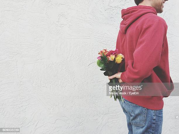 midsection of man hiding flower bouquet back against wall - hands behind back stock pictures, royalty-free photos & images
