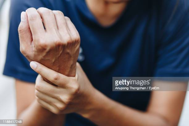 midsection of man holding aching wrist - wrist stock pictures, royalty-free photos & images
