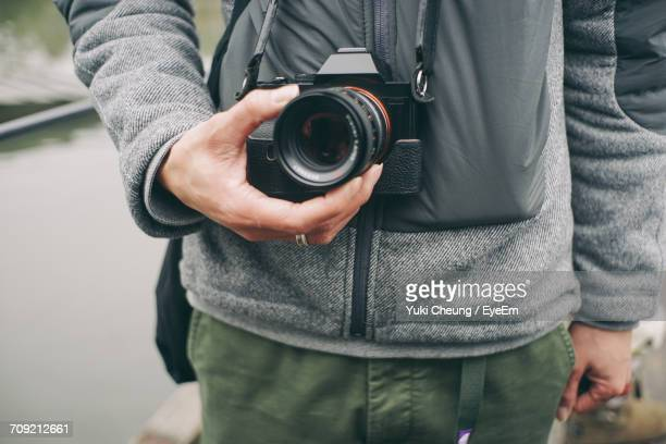 Midsection Of Man Holding Analog Camera