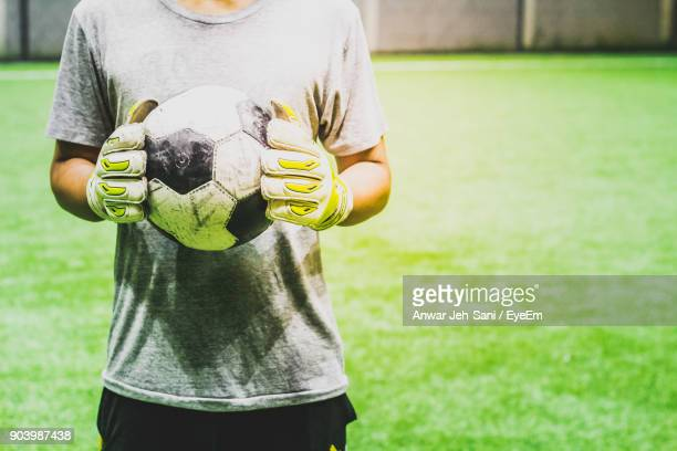 midsection of man holding ball while standing on grass - mid section stock photos and pictures