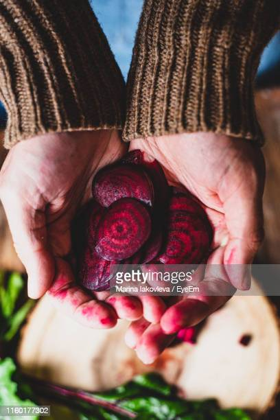 Midsection Of Man Holding Beetroot On Table