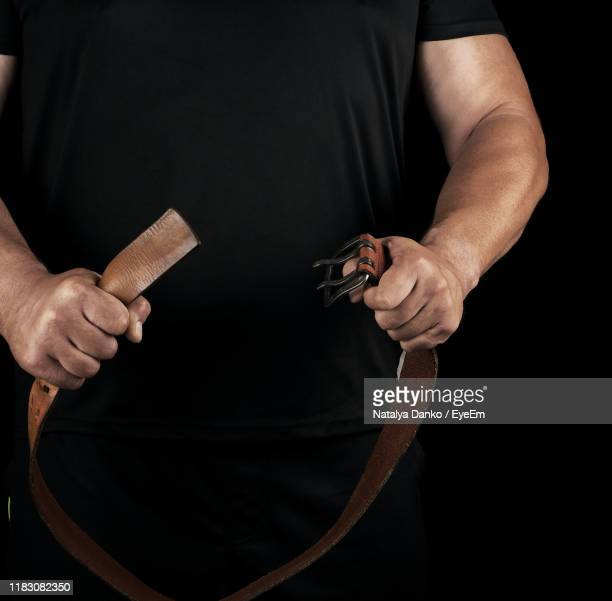 midsection of man holding belt against black background - belt stock pictures, royalty-free photos & images