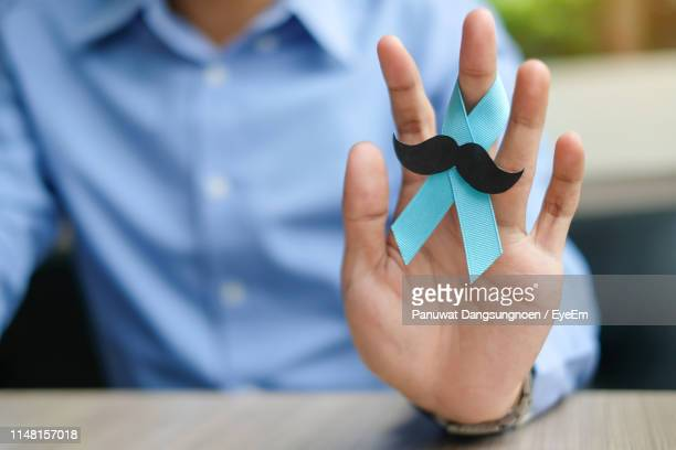 midsection of man holding blue ribbon with mustache - blue cancer ribbon stock photos and pictures