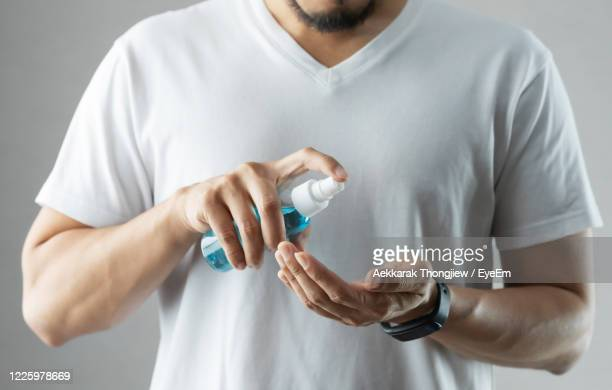 midsection of man holding bottle and standing against white background - rubbing alcohol stock pictures, royalty-free photos & images