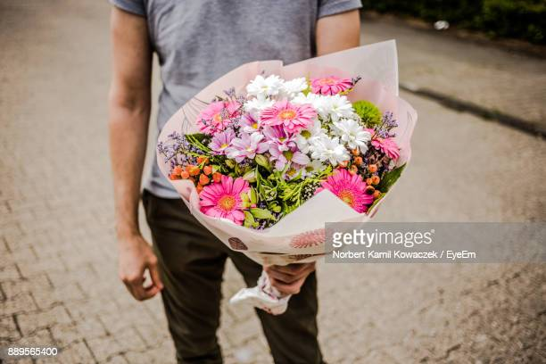 midsection of man holding bouquet while standing on street - bouquet foto e immagini stock