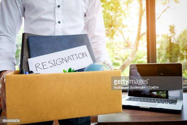 midsection of man holding box with resignation letter by table at office - quitting a job stock pictures, royalty-free photos & images
