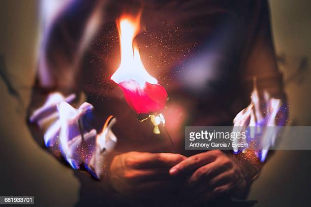 Midsection Of Man Holding Burning Rose