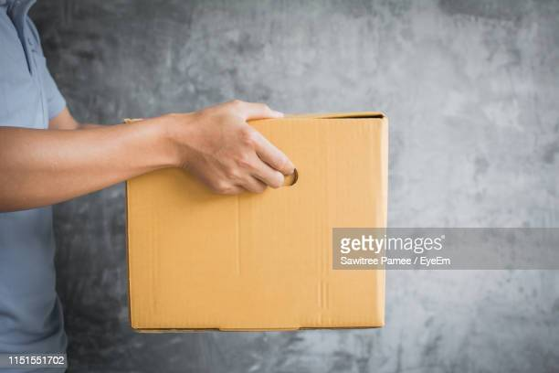 midsection of man holding cardboard box against wall - send stock pictures, royalty-free photos & images