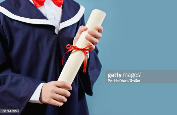 midsection of man holding certificate while standing against blue background - graduation background stock pictures, royalty-free photos & images