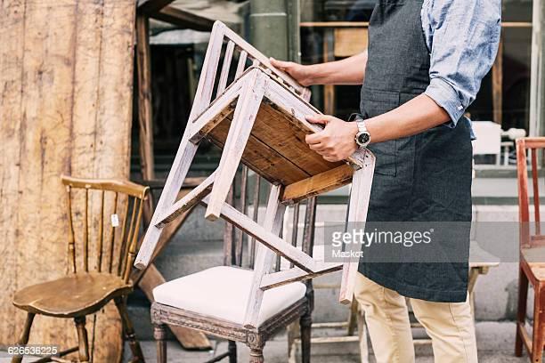 midsection of man holding chair while standing against store - só um homem maduro imagens e fotografias de stock