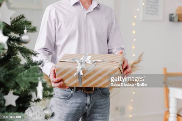 Midsection Of Man Holding Christmas Present