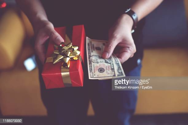 midsection of man holding christmas present with money at home - christmas cash stock pictures, royalty-free photos & images