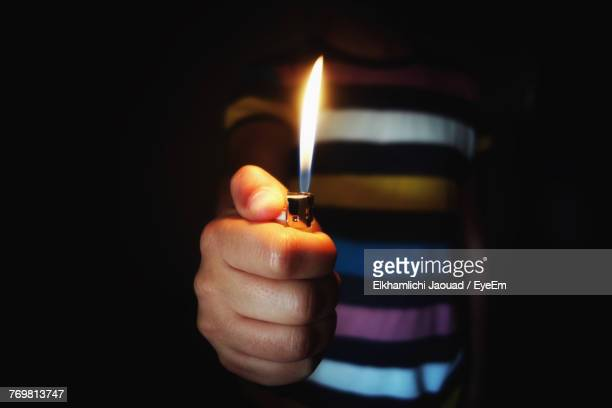 midsection of man holding cigarette lighter in darkroom - cigarette lighter stock pictures, royalty-free photos & images