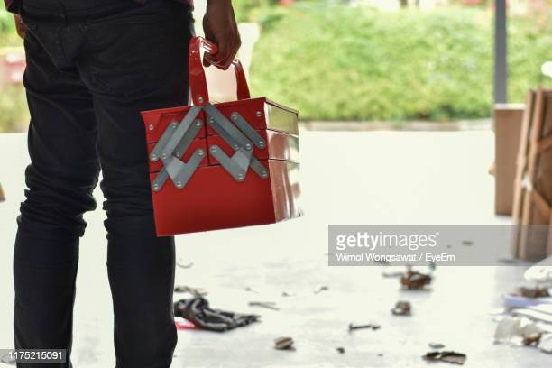 midsection of man holding container while standing on road - wimol wongsawat stock photos and pictures