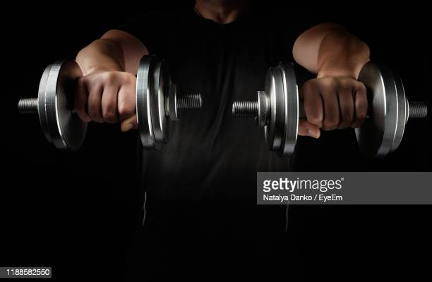 midsection of man holding dumbbells while standing against black background - dumbbell stock pictures, royalty-free photos & images