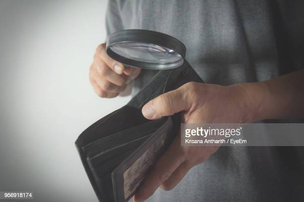 Midsection Of Man Holding Empty Wallet And Magnifying Glass Against Gray Background
