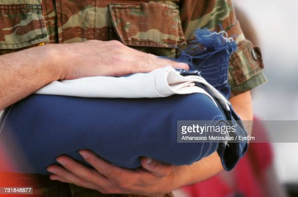 midsection of man holding fabric - folded flag stock pictures, royalty-free photos & images