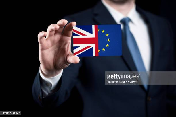 midsection of man holding flag against black background - brexit stock pictures, royalty-free photos & images