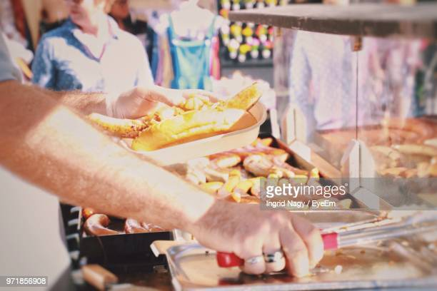 Midsection Of Man Holding Food For Sale At Market