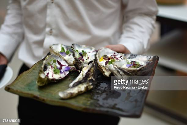 midsection of man holding food in plate - oyster shell stock photos and pictures