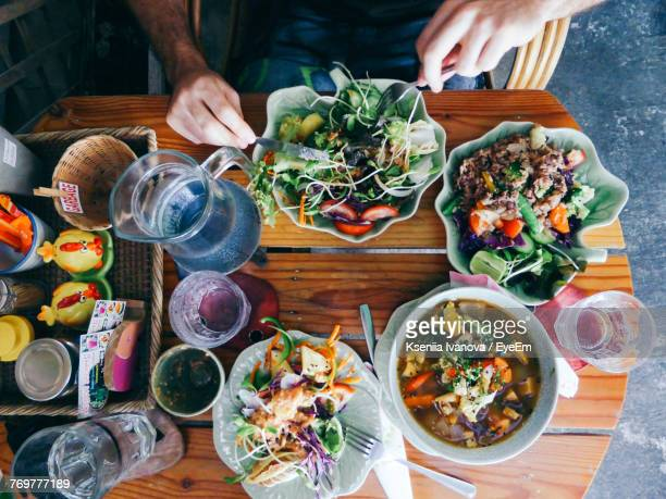 midsection of man holding fork and spoon on salad - chiang mai province stock photos and pictures