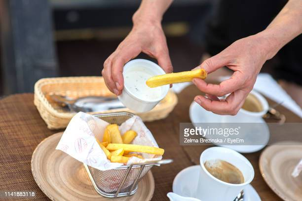 Midsection Of Man Holding French Fries With Sauce In Container Over Restaurant Table