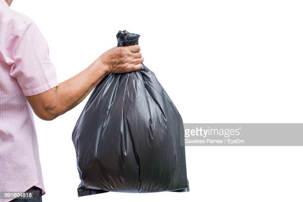 midsection of man holding garbage bag against white background - ゴミ袋 ストックフォトと画像