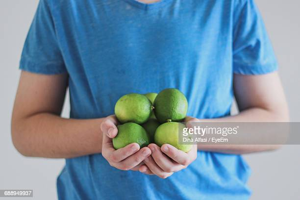 Midsection Of Man Holding Green Limes Against White Background