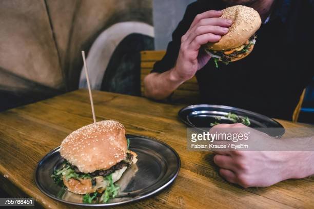 Midsection Of Man Holding Hamburger At Table In Restaurant
