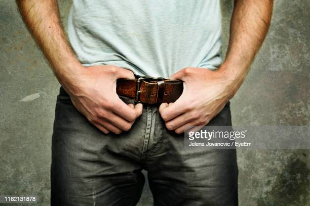 midsection of man holding his belt against wall - hands in her pants stock pictures, royalty-free photos & images