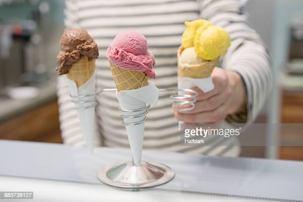 Midsection of man holding ice cream cone by stand at store
