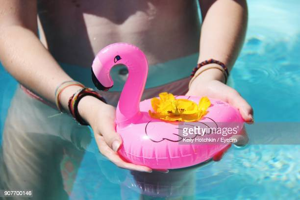 Midsection Of Man Holding Inflatable Duck In Swimming Pool