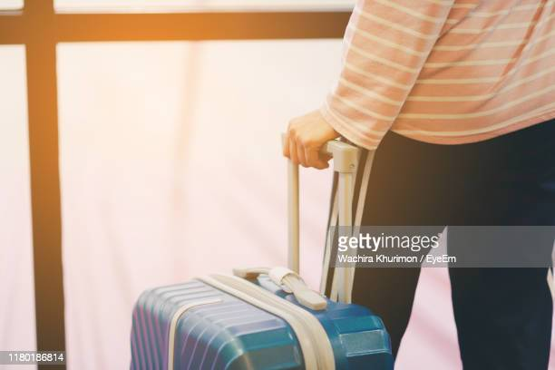 midsection of man holding luggage - 取っ手 ストックフォトと画像