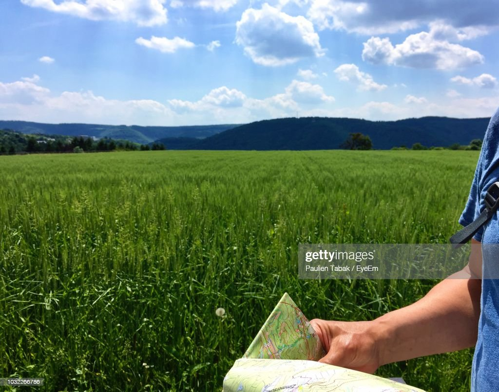 Midsection Of Man Holding Map On Grassy Landscape During Sunny Day : Stockfoto