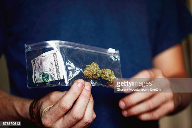 Midsection Of Man Holding Marijuana In Plastic Bag