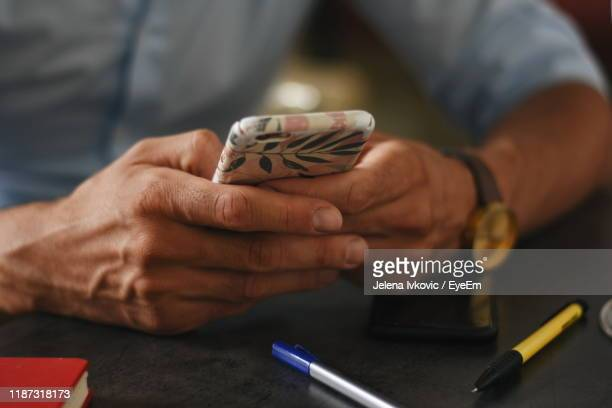 midsection of man holding mobile phone on table - jelena ivkovic stock pictures, royalty-free photos & images