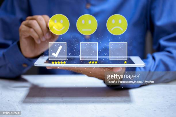 midsection of man holding mobile phone on table - customer engagement stock pictures, royalty-free photos & images