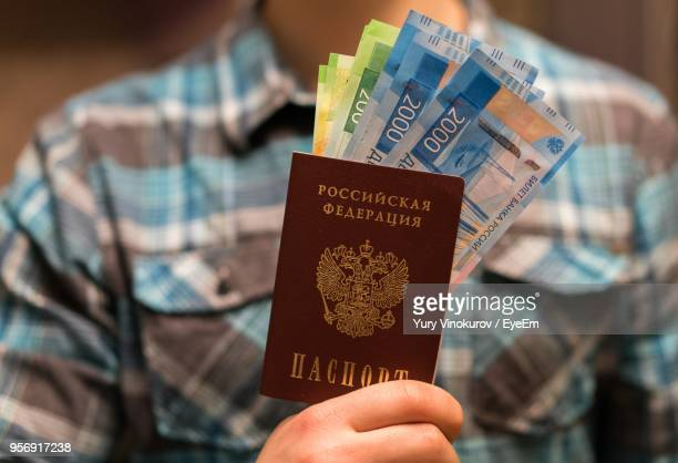Midsection Of Man Holding Money And Passport