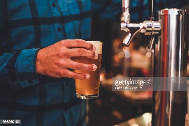 midsection of man holding of beer glass - brewery stock pictures, royalty-free photos & images