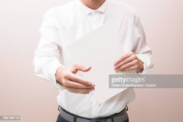 Midsection Of Man Holding Paper Against White Background