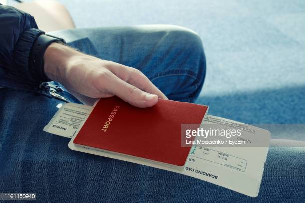 midsection of man holding passport - airplane ticket stock pictures, royalty-free photos & images