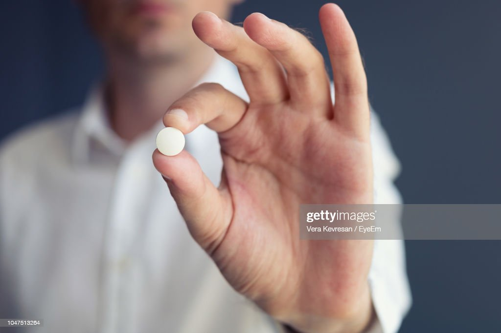 Midsection Of Man Holding Pill : Stock Photo