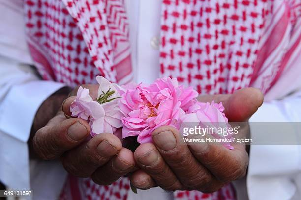 midsection of man holding pink roses - saudi arabia stock photos and pictures