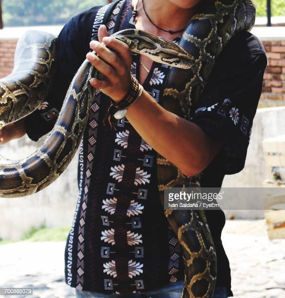 Midsection Of Man Holding Python While Standing On Field